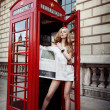Stock Photo: Attractive blonde with long slim legs in high heels standing in red phone box in center on London City and covering her body with fresh newspaper