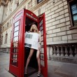 Stock Photo: Beautiful blond with long slim legs standing in red phone box in center on London City and covering her body with fresh newspaper
