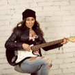 Young teenage looking woman playing her black electronic guitar wearing her leather jacket and knitted beanie standing in front of white brick wall — Stock Photo #41874765