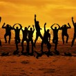 Stock Photo: Male friends are having fun at summer and jumping up on the sunset near the sea putting their hands up to the orange sky