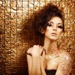 Stock Photo: Portrait of beautiful female in golden shimmery glitter and sparkles with skin covered foil is in club