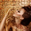 Stock Photo: Attractive addicted hot brunette with beautiful golden makeup and gold caramel painted hands is posing in front of abstract golden background