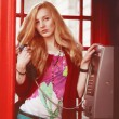 Stock Photo: Attractive british womwith light red hair is standing in traditional london phone box with telephone in her hands and looking to camera