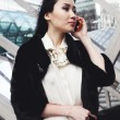 Stock Photo: Beautiful asibusiness womin London standing on street in city and talking by mobile phone