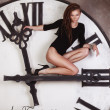 Slim and sexy dancer sitting on the large clock arrows — Zdjęcie stockowe