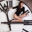 Foto de Stock  : Slim and sexy dancer sitting on the large clock arrows