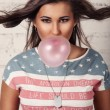 Stock Photo: Young americfemale is chewing her gum and blowing bubbles out of it
