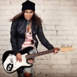 Young teenage looking woman playing her black electronic guitar wearing her leather jacket and knitted beanie standing in front of white brick wall — Stock Photo