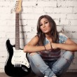 Stock Photo: Young female musiciis sitting on floor near to her guitar