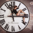 Foto Stock: Sexy and attractive female is sitting on giant clock arrows counting time