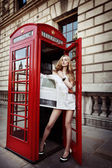 Attractive blonde with long slim legs in high heels standing in the red phone box in the center on London City and covering her body with a fresh newspaper — Stock Photo