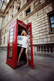 Beautiful blond with long slim legs standing in the red phone box in the center on London City and covering her body with a fresh newspaper — Stock Photo