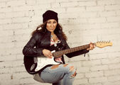 Young teenage looking woman playing her black electronic guitar wearing her leather jacket and knitted beanie standing in front of white brick wall — Photo
