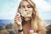 Portrait of young caucasian woman blowing soap bubbles at summer sitting on the stones near the sea in front of cloudy sky background — Stock Photo