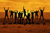 Male friends are having fun at summer and jumping up on the sunset near the sea putting their hands up to the orange sky — Stock Photo