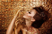 Attractive addicted hot brunette with beautiful golden makeup and gold caramel painted hands is posing in front of abstract golden background — Stock Photo
