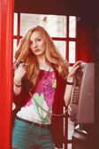 Attractive british woman with light red hair is standing in the traditional london phone box with telephone in her hands and looking to the camera — Stock Photo