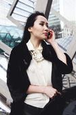 Beautiful asian business woman in London standing on the street in the city and talking by the mobile phone — Stock Photo