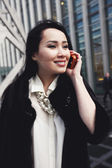 Confident asian business woman with smile on her face standing in London on the street in the city and talking by the mobile phone — Stock Photo