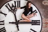Slim and sexy dancer sitting on the large clock arrows — Stock Photo