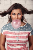Young american female is chewing her gum and blowing bubbles out of it — Stock Photo