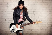 Young teenage looking woman playing her black electronic guitar wearing her leather jacket and knitted beanie standing in front of white brick wall — Стоковое фото