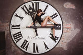 Sexy and attractive female is sitting on the giant clock arrows counting time — Stok fotoğraf