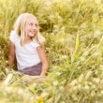 Girl sitting in wheatfield — Stock Photo #11624470