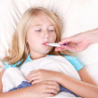 Sick girl with a thermometer in mouth — Stock Photo