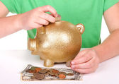 Child putting money in piggy bank — Stock Photo