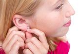 Teen putting in ear ring — Stock Photo