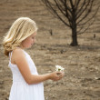 Girl holding flower in baren landscape — Stock Photo