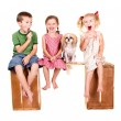 Three kids sitting on a bench eating lolli pops — Stock Photo #13890734