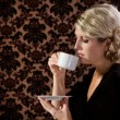 Retro looking woman drinking tea or coffee — Stock Photo