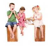 Three kids sitting on a bench eating lolli pops — Stock Photo