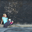Girl sitting on ground next to brick wall — Stock Photo #13949557