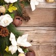 Christmas flowers and pine branches on wood - Stock Photo