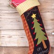 Christmas stocking with presents on wood — Stock Photo