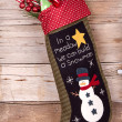 Christmas stocking with presents on wood — Stock Photo #13950084