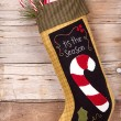 Christmas stocking with presents on wood - Stock Photo