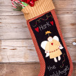 Christmas stocking with presents on wood — Stock Photo #13950095