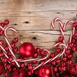 Candy canes and ornaments on wood — Stock Photo