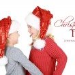Two children wearing Santa hats — Stock Photo #17437297