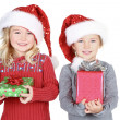 Two children holding presents wearing Santa hats — Stock Photo #17437381