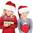 Two children holding presents wearing Santa hats — Stock Photo