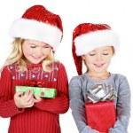 Two children holding presents wearing Santa hats — Stock Photo #17437385
