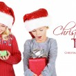Two children holding presents wearing Santa hats — Stock Photo #17437389
