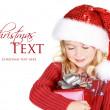 Child holding present wearing santa hat — Stock Photo
