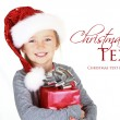 Child holding present wearing santa hat — Stok fotoğraf