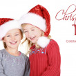 Two children wearing Santa hats — Stock Photo #17437469